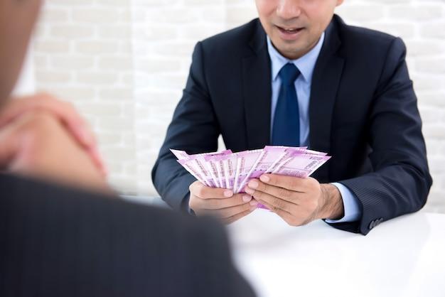 Empresário, recebendo recompensa em dinheiro em forma de dinheiro de notas de rúpia indiana Foto Premium