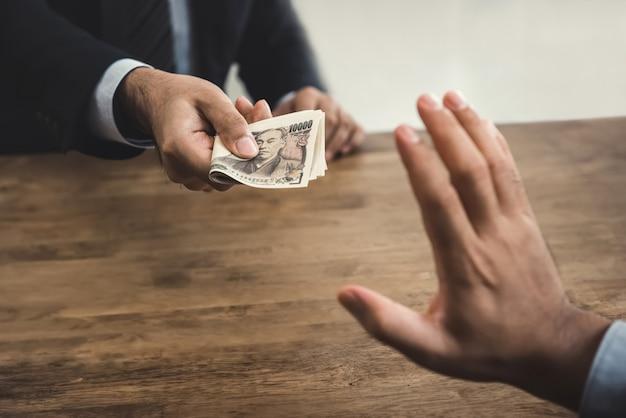 Empresário, rejeitando dinheiro moeda iene japonês de seu parceiro Foto Premium