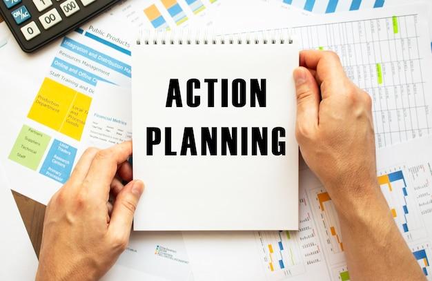 Empresário segura o bloco de notas com o texto planejamento de ações. gráficos financeiros no desktop. conceito financeiro e de negócios. Foto Premium