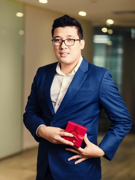 Empresário, segurando a caixa de presente vermelha Foto Premium