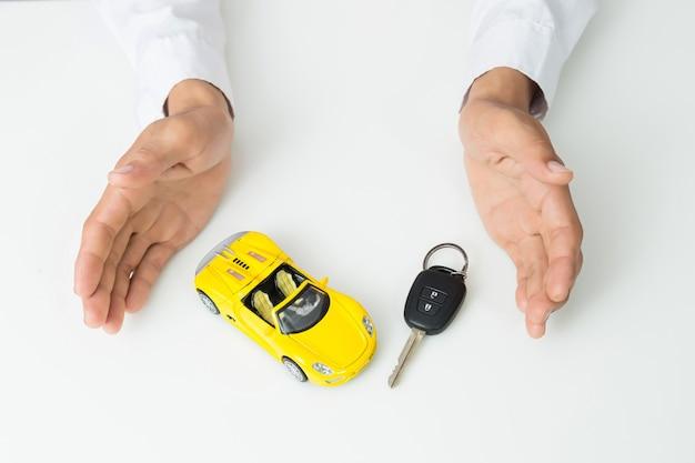 Empresário, segurando as chaves do carro e modelo de carro em miniatura Foto Premium