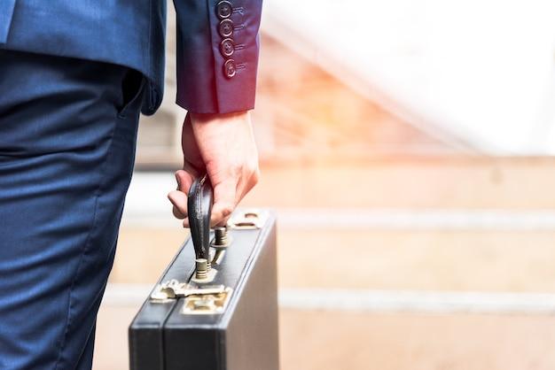 Empresário segurando maleta e indo trabalhar Foto Premium