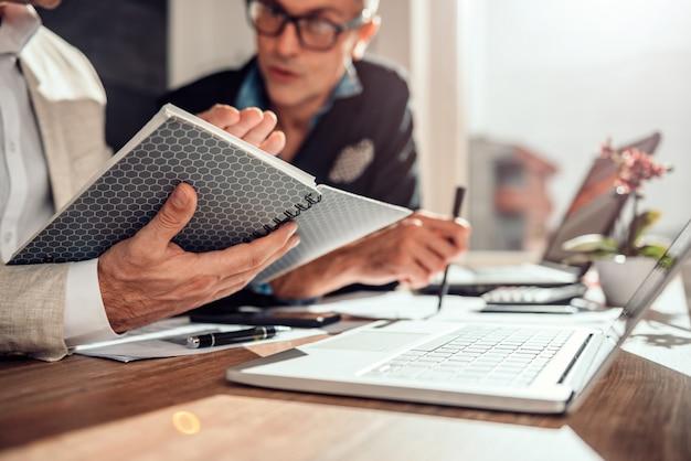 Empresário, segurando o bloco de notas durante uma reunião Foto Premium