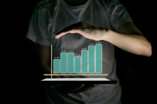 Empresário segurando o tablet e mostrando um holograma virtual crescente de estatísticas Foto Premium