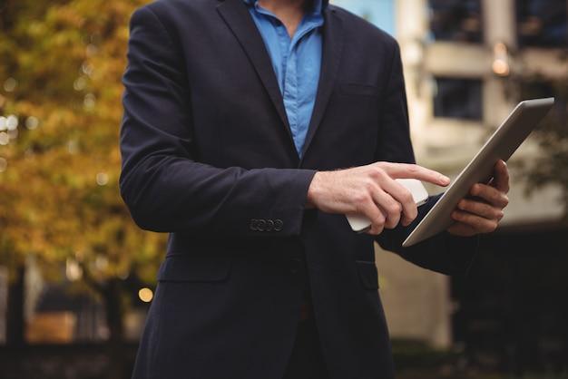 Empresário, segurando o telefone móvel e usando tablet digital Foto gratuita