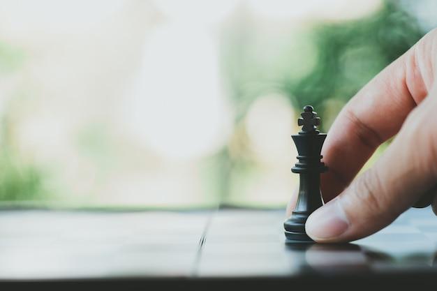 Empresário segurando um rei xadrez é colocado em um tabuleiro de xadrez. Foto Premium