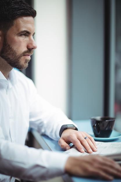 Empresário sentado à mesa e lendo jornal no escritório Foto Premium