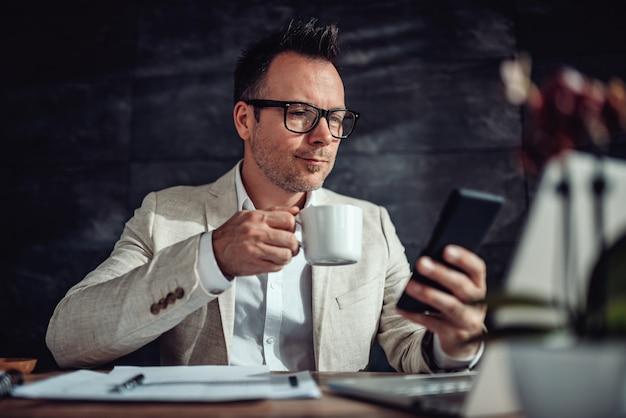 Empresário sentado em sua mesa, tomando café e usando telefone inteligente Foto Premium