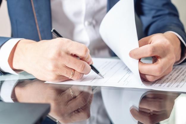 Empresário sentado na mesa assinando documentos no escritório de perto Foto Premium