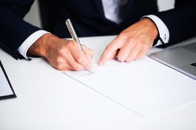 Empresário sentado na mesa de escritório, assinando contrato Foto Premium