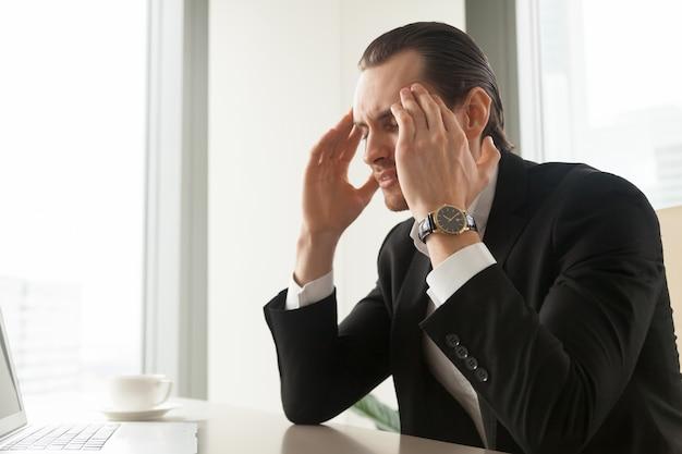 Empresário sofre de enxaqueca ou dor de cabeça Foto gratuita