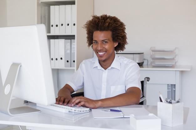 Empresário sorridente casual em cadeira de rodas trabalhando em sua mesa Foto Premium