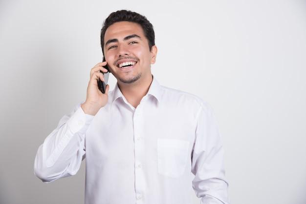 Empresário sorridente, falando com o telefone em fundo branco. Foto gratuita