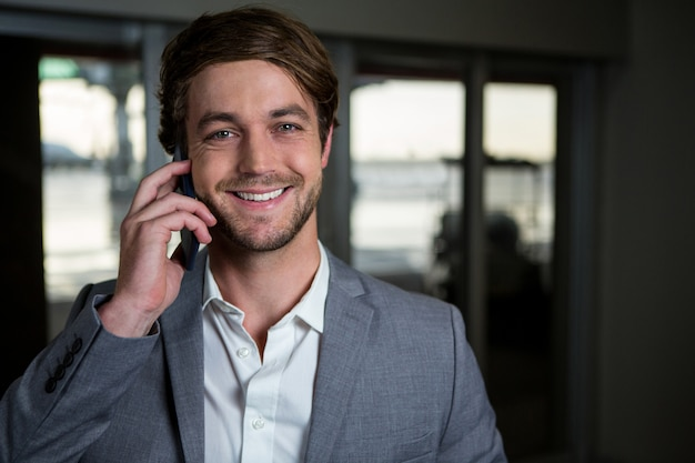 Empresário sorridente falando em seu telefone celular no terminal do aeroporto Foto gratuita