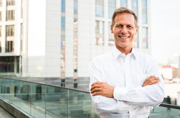 Empresário sorrindo com os braços cruzados Foto gratuita