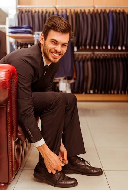 Empresário sorrindo e experimentando sapatos clássicos. Foto Premium