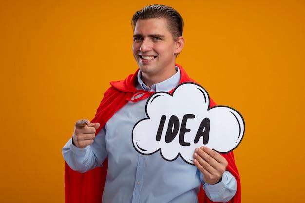 Empresário super-herói com capa vermelha segurando um cartaz de bolha do discurso com a ideia da palavra apontando com o dedo indicador para a câmera, sorrindo em pé sobre um fundo laranja Foto gratuita