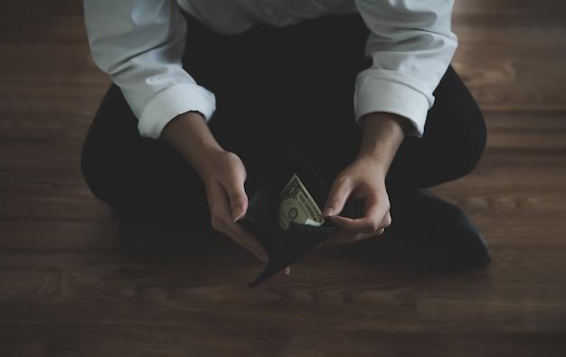 Empresário tem problema financeiro e falha em seu negócio sentado carteira aberta com uma nota de dólar dos eua Foto Premium