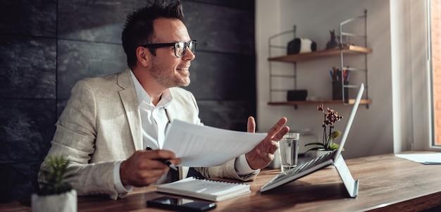 Empresário tendo reunião on-line em seu escritório Foto Premium