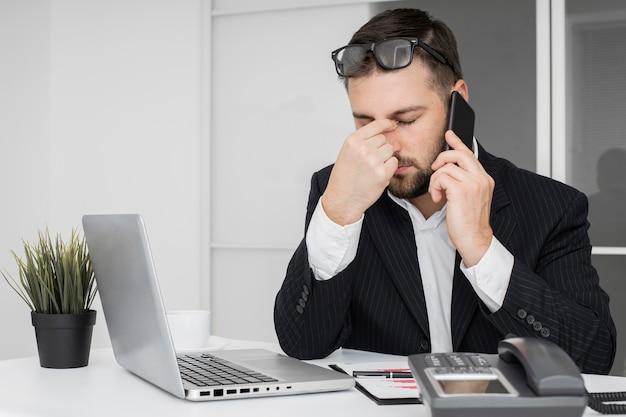 Empresário tendo um dia difícil no escritório Foto gratuita