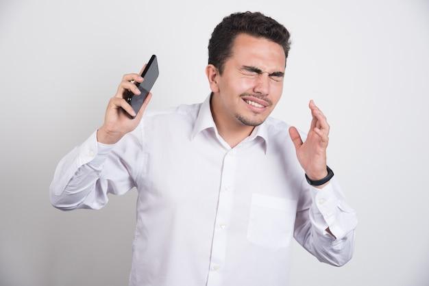 Empresário tentando fugir do telefone em fundo branco. Foto gratuita