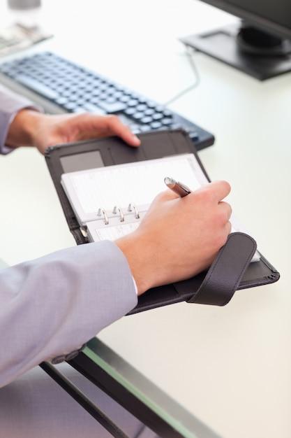 Empresário tomando notas no calendário de bolso Foto Premium