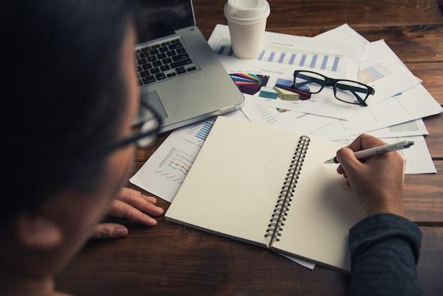 Empresário, trabalhando com o laptop no escritório de espaço aberto. relatório de reunião em andamento. Foto Premium