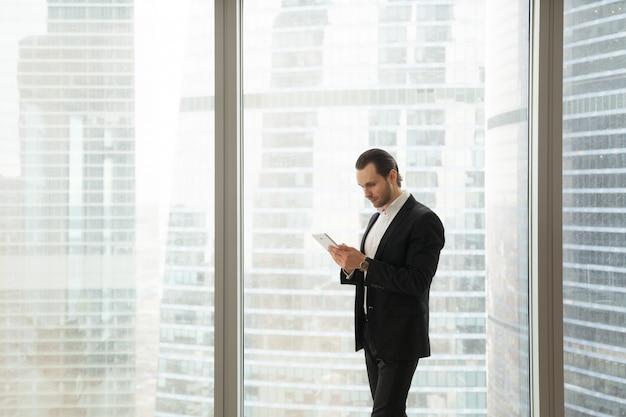 Empresário, trabalhando em tablet perto de grande janela Foto gratuita