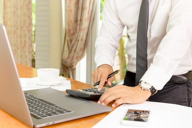 Empresário, trabalhando na calculadora para calcular o plano financeiro Foto Premium
