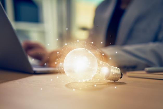 Empresário, trabalhando no laptop e lâmpada em cima da mesa com inovação e criatividade são as chaves para o sucesso. Foto Premium
