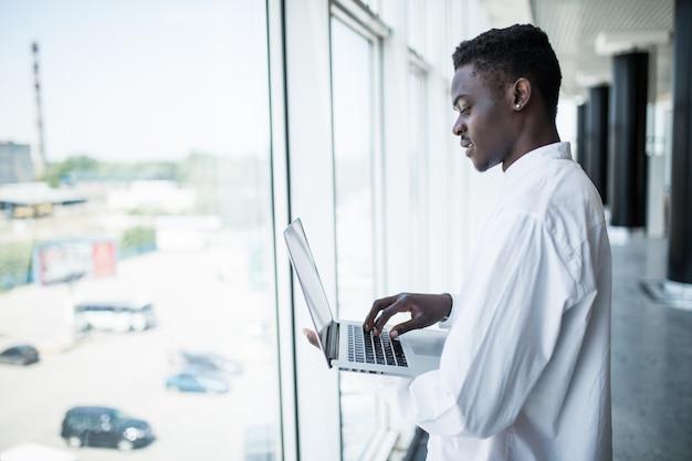 Empresário trabalhando no laptop no escritório moderno Foto gratuita