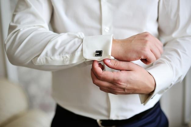 Empresário usa uma camisa e abotoaduras no escritório Foto Premium
