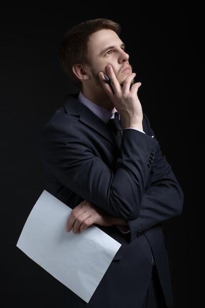 Empresário vale a pena pensar com caneta e folha de papel Foto Premium