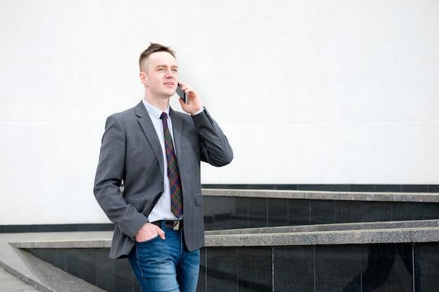Empresário, vestido com uma jaqueta cinza, calça jeans, camisa branca e gravata, sai do business center e fala ao telefone enquanto caminha Foto Premium