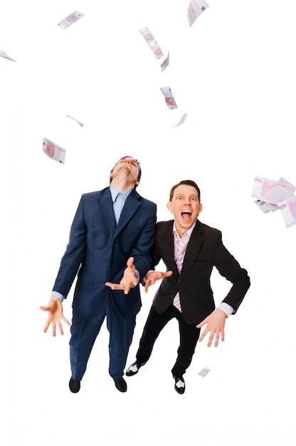 Empresários alegres vomitando um monte de euros Foto gratuita