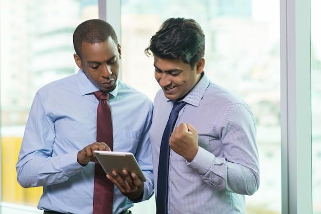 Empresários animados lendo boas notícias no computador tablet Foto gratuita