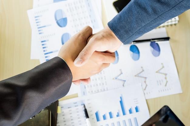 Empresários apertando as mãos durante uma reunião Foto gratuita