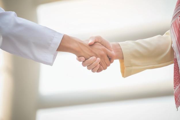 Empresários árabes apertam as mãos e aceitam negócios para o trabalho em equipe. Foto Premium
