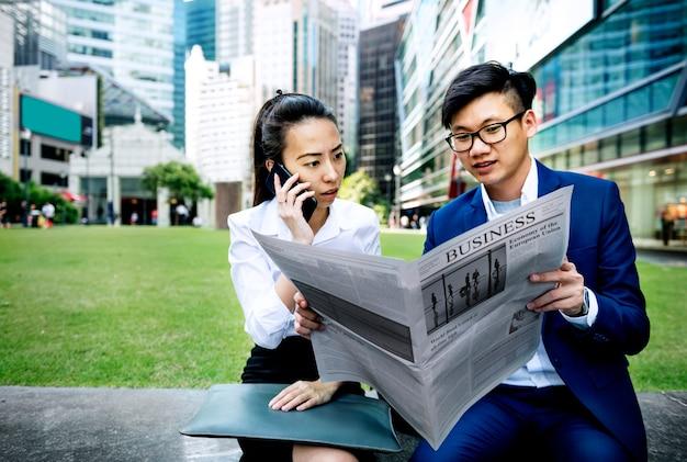 Empresários asiáticos lendo o jornal Foto gratuita