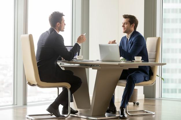 Empresários bem sucedidos analisando perspectivas Foto gratuita
