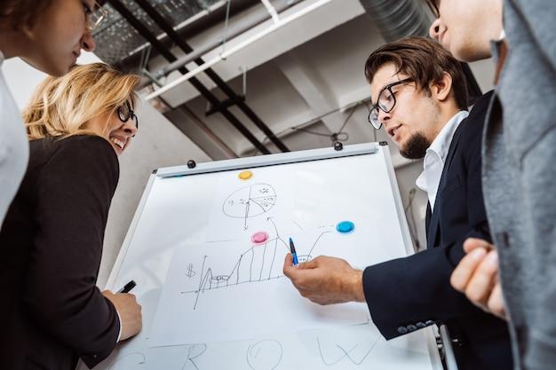 Empresários com quadro branco, discutindo a estratégia em uma reunião Foto gratuita