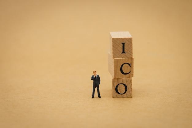 Empresários de pessoas em miniatura de pé com palavra de madeira ico (oferta de moeda inicial) Foto Premium