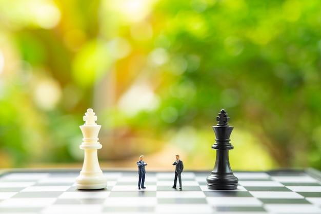 Empresários de pessoas em miniatura, de pé sobre um tabuleiro de xadrez com uma peça de xadrez Foto Premium
