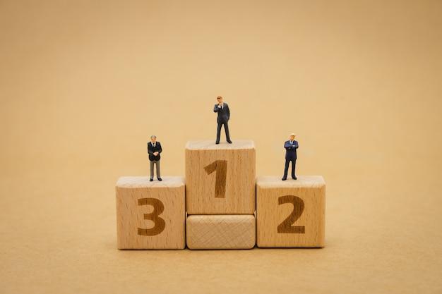 Empresários de pessoas em miniatura em pé na submissão do prêmio de pódio. Foto Premium