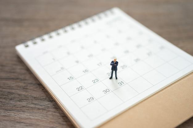 Empresários de pessoas em miniatura no calendário branco usando como conceito de negócio de plano de fundo Foto Premium