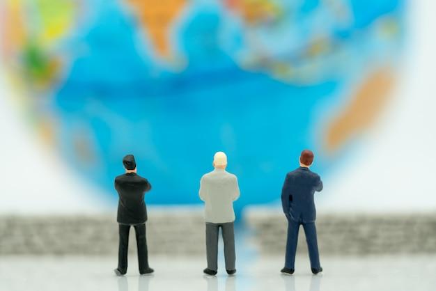 Empresários em miniatura e o globo Foto Premium