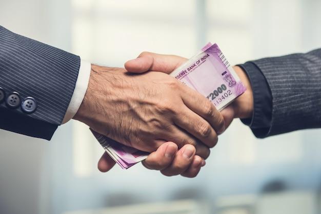 Empresários fazendo aperto de mão com dinheiro, moeda rupia indiana, nas mãos Foto Premium