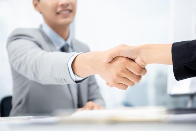 Empresários fazendo aperto de mão na sala de reuniões no escritório da cidade Foto Premium