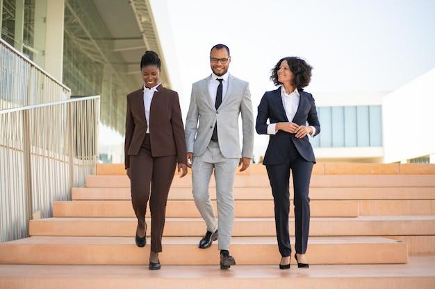 Empresários felizes andando perto do prédio de escritórios Foto gratuita