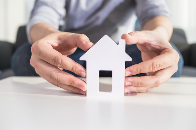 Empresários mantêm modelo de casa na mão Foto gratuita